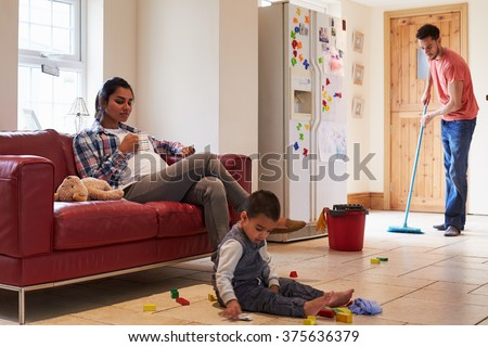 Father Mops Floor As Pregnant Mother Relaxes On Sofa - stock photo