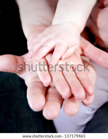 Father, mother and baby holding hands. Close up - stock photo