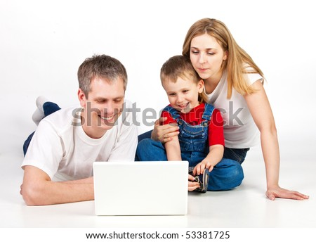 Father, mother and child lying on the floor with laptop - stock photo