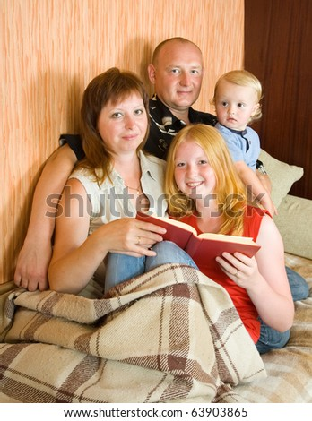Father, mother and children reading  book at home - stock photo