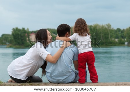 Father, mother and daughter - family on the river bank