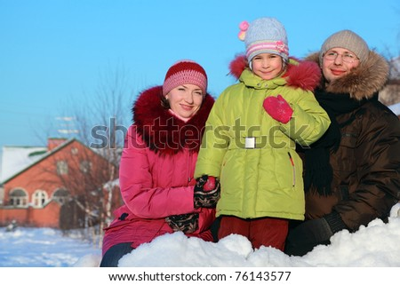 father, mother and daughter standing outdoors in winter near house, mother holding daughter hand - stock photo