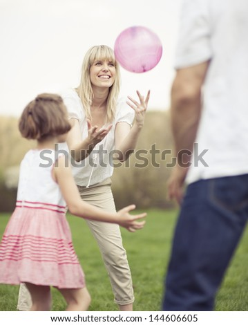 Father mother and daughter throwing ball to each other in the park - stock photo