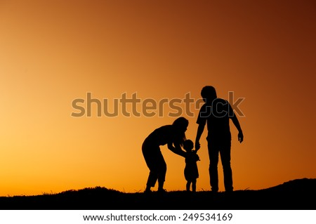 father mother and son playing outdoors at sunset silhouette - stock photo