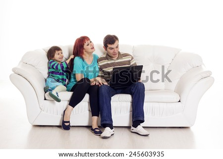 Father, mother and son sitting on the sofa with notebook over white background