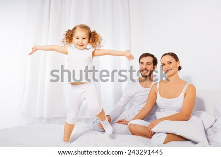 Father, mother and their cute daughter playing - stock photo