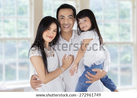 Father, mother, and their daughter smiling on camera at home - stock photo
