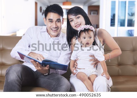 Father, mother and their daughter spending time in the living room while looking at the camera,