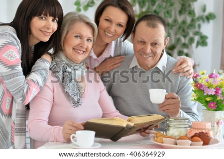 father, mother and two daughter together at the table drinking tea - stock photo
