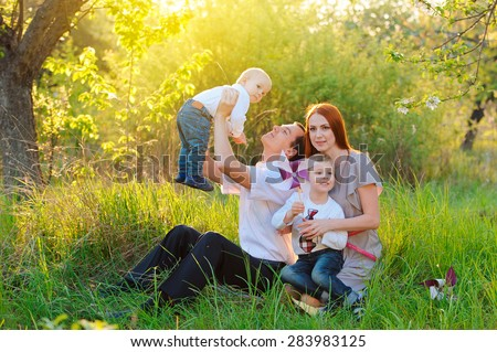 Father, mother and two sons are playing in the garden on sunset