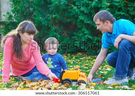 father, mother and young son at a picnic in the park.