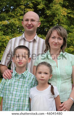 father, mother, little boy and girl in early fall park. all of them except father looking at camera. - stock photo