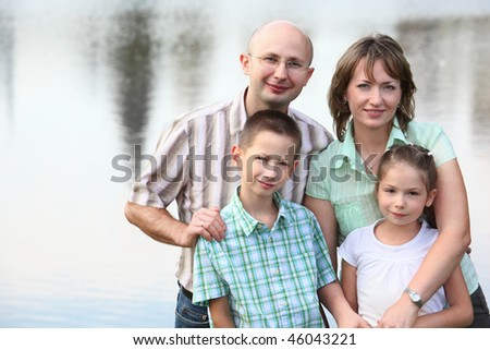 father, mother, son and daughter on pond background. - stock photo