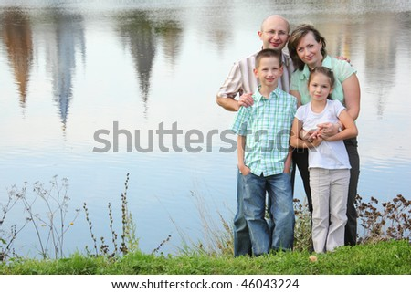 father, mother, son and daughter staying near pond. mother is embracing her daughter - stock photo