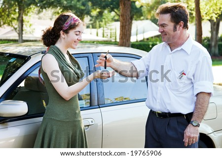 Father or driving instructor handing over the keys to a new young driver.