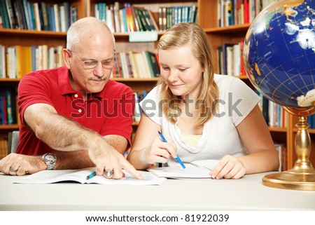 Father or teacher helping teen girl with homework.