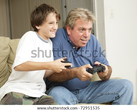 Father or uncle playing video games with a little boy - his son or nephew. - stock photo