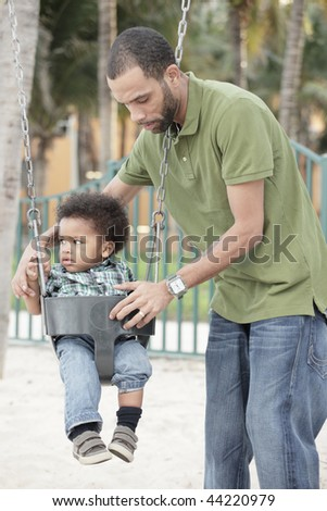 Father placing his son on a swing - stock photo