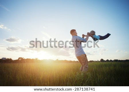 father playing and spinning with his son in the park (intentional sun glare) - stock photo