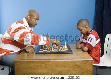 Father playing chess with his boy - stock photo