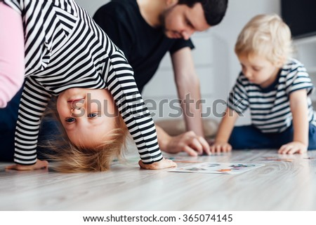 Father playing puzzle with children. Girl doing exercises on the floor. - stock photo