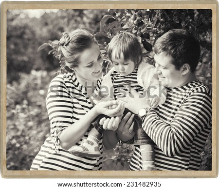 father playing with baby on nature black and white vintage card