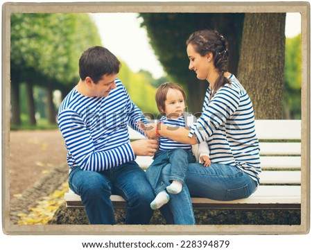 father playing with baby on nature vintage card - stock photo