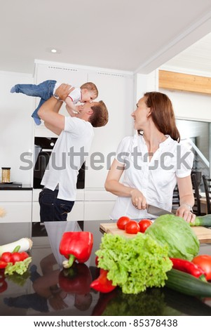 Father playing with child while mother cuts vegetables in kitchen - stock photo