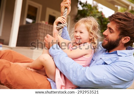 Father playing with daughter on a rope swing in a garden - stock photo