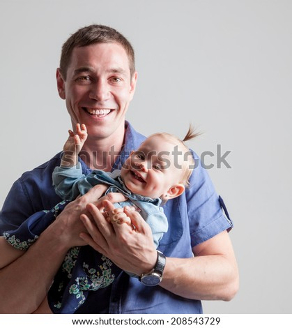 Father playing with his daughter holding her in his arms. - stock photo