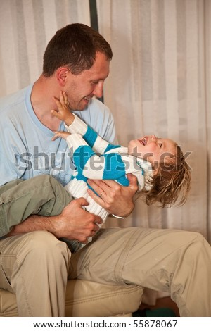 Father playing with his little duaghter on the sofa. - stock photo