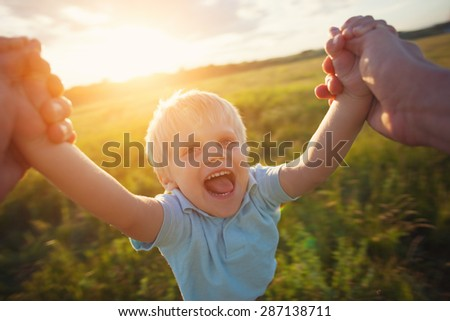 father playing with his son in the park (intentional sun glare and motion blur) - stock photo