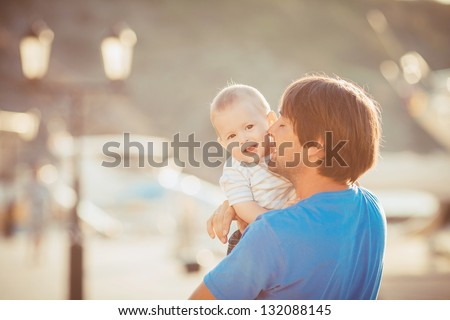 Father playing with his son on the pier near yacht club in summer. Outdoor - stock photo
