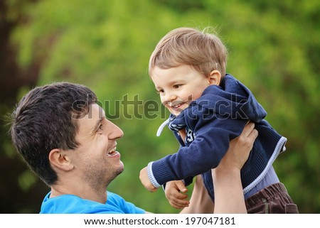 father playing with his son, shallow DOF - stock photo
