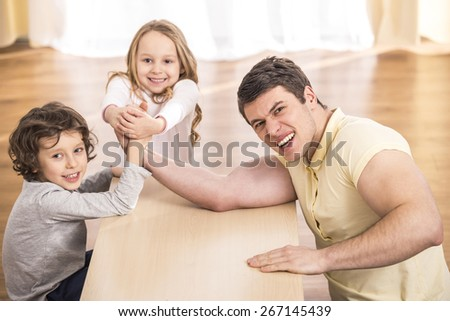Father playing with kids in living room. - stock photo