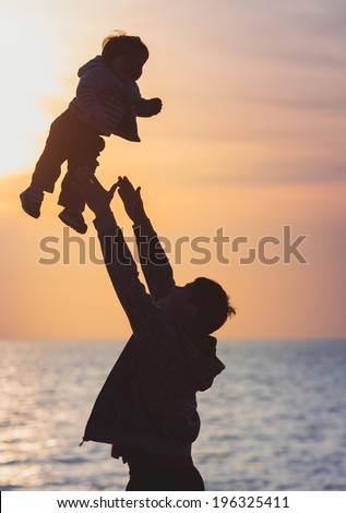 Father playing with little son on sunset  - stock photo