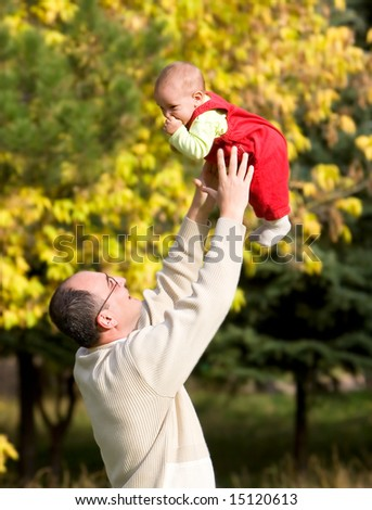 father playing with son in autumn park - stock photo