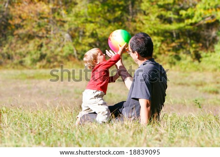 father playing with son outdoors - stock photo