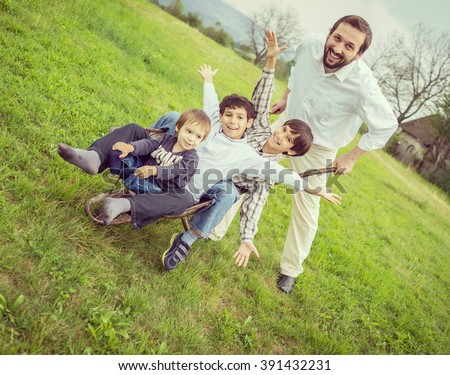 Father playing with sons using trolley on meadow - stock photo