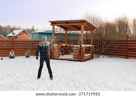 father plays with child snowballs in the backyard - stock photo