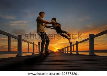 Father plays with his girl on the beach at sunset on wooded bridge - stock photo