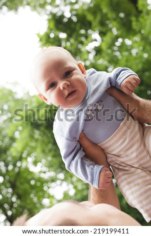 Father plays with son in a park. Flying baby - stock photo