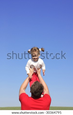 father plays with the daughter on a background of the sky