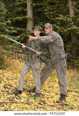 father pointing and guiding son on first deer hunt - stock photo
