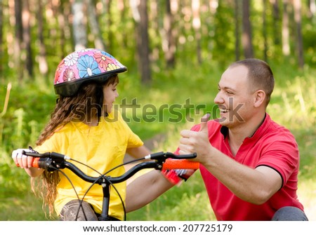 father praises his daughter, who learned to ride a bike - stock photo