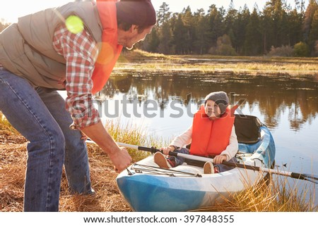Father preparing launch for son in kayak on lakeside - stock photo