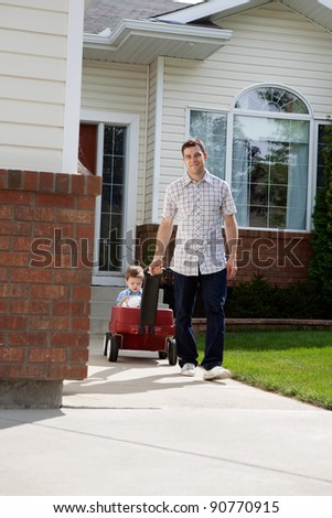 Father pulling son sitting with a ball in pram down a walkway