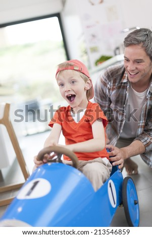 father pushing his boy in a pedal car - stock photo