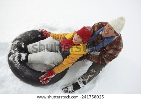Father pushing son on snow tube - stock photo