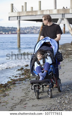 Father pushing wheelchair with disabled son on beach